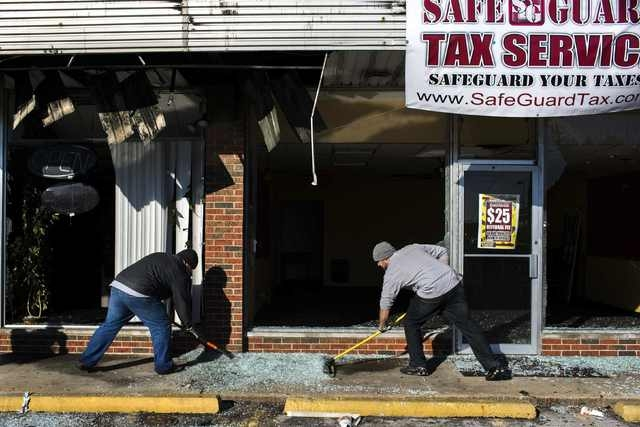 Volunteers work to clean a sidewalk outside of a business that had been burned and damaged following a night of rioting in Ferguson, Missouri November 25, 2014. (REUTERS/Lucas Jackson)