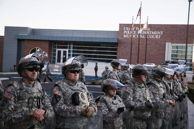 National Guard soldiers stand in formation outside the Ferguson, Missouri, Police Department, Tuesday, Nov. 25, 2014. At least a dozen stores have been set ablaze and others looted in Ferguson in  ...
