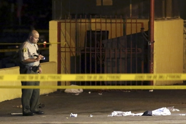"Los Angeles County Sheriff's deputies stand near the scene where a pedestrian was killed in a hit-and-run crash reportedly involving rap mogul Marion ""Suge"" Knight, in Compton, California, Thursda ..."