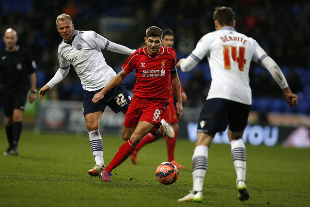 Liverpool's Steven Gerrard (C) is challenged by Bolton Wanderers' Eidur Gudjohnsen (L) and Dorian Dervite during their FA Cup fourth round replay soccer match at the Macron Stadium in Bolton, nort ...