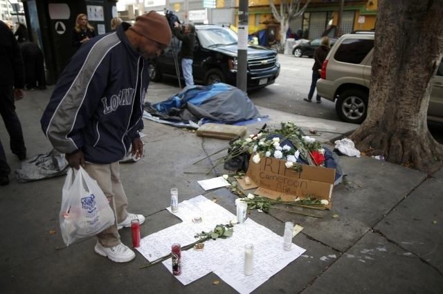 A man views a memorial for a man killed by police on skid row in Los Angeles, March 2, 2015. Los Angeles police officers trying to subdue a robbery suspect in the city's skid row section shot and  ...