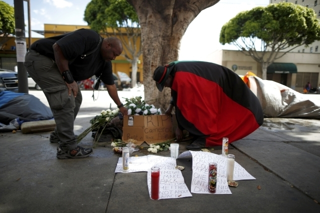 Gerald Pitts, right, puts a rose on a memorial for a man killed by police on skid row in Los Angeles, March 2, 2015. Los Angeles police officers trying to subdue a robbery suspect in the city's sk ...