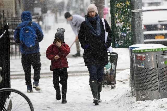 A woman and a child walk through a snow storm in New York March 3, 2015.    (REUTERS/Lucas Jackson)