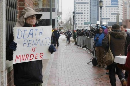 "Joe Kebartas holds a sign reading ""Death Penalty is Murder"" outside the trial of accused Boston Marathon bomber Dzhokhar Tsarnaev in Boston, Wednesday, March 4, 2015. (Reuters/Brian Snyder)"