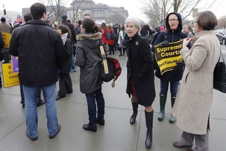 Former U.S. Health and Human Services Secretary Kathleen Sebelius, center, walks between demonstrators as she arrives at the Supreme Court building in Washington, Wednesday, March 4, 2015. (Reuter ...