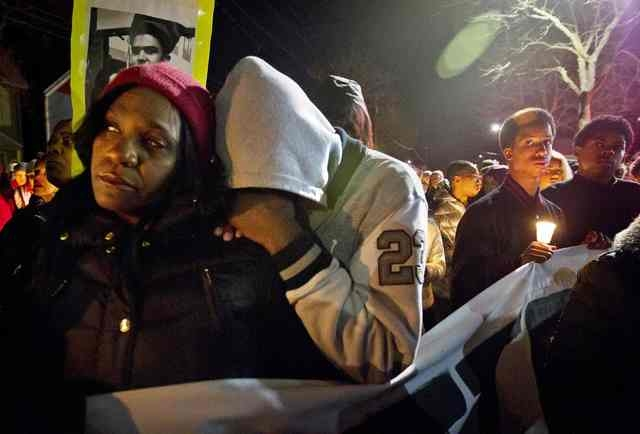 Tramale Robinson rests his head on the shoulder of his mother Lynn Robinson (L) during a candlelight vigil for Tony Robinson Jr. in Madison, Wisconsin, March 8, 2015.  (REUTERS/Ben Brewer)