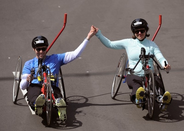 Boston Marathon bombing survivors Jessica Kensky and her husband Patrick Downes (L) cross the finish line at the 118th running of the Boston Marathon in Boston, Massachusetts April 21, 2014. (REUT ...