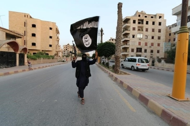 A member loyal to the Islamic State in Iraq and the Levant (ISIL) waves an ISIL flag in Raqqa, June 29, 2014. (REUTERS/Stringer)
