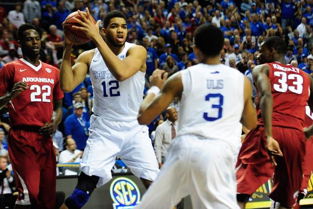Mar 15, 2015; Nashville, TN, USA; Kentucky Wildcats forward Karl-Anthony Towns (12) keeps the ball away from Arkansas Razorbacks forward Jacorey Williams (22) during the second half of the SEC Con ...