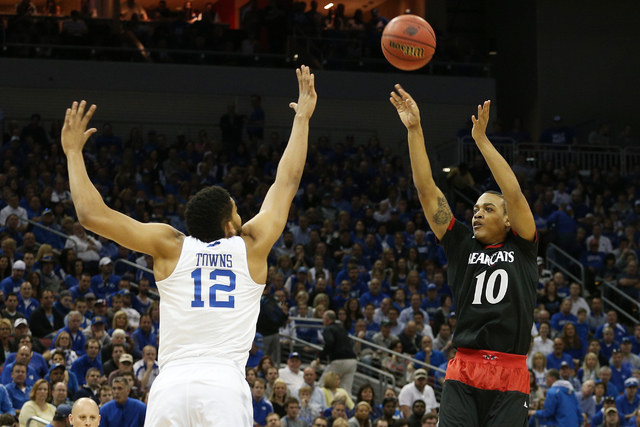 Mar 21, 2015; Louisville, KY, USA; Cincinnati Bearcats guard Troy Caupain (10) shoots the ball against Kentucky Wildcats forward Karl-Anthony Towns (12) during the first half in the third round of ...