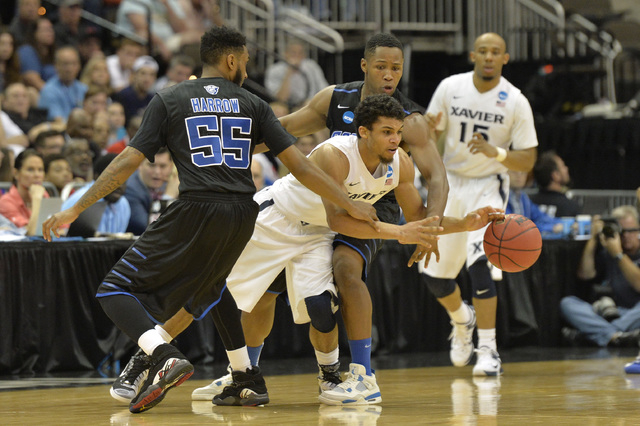 Mar 21, 2015; Jacksonville, FL, USA; Xavier Musketeers guard Dee Davis (11) loses the ball as he is trapped by Georgia State Panthers guard Ryan Harrow (55) and Panthers guard Isaiah Dennis (4) in ...