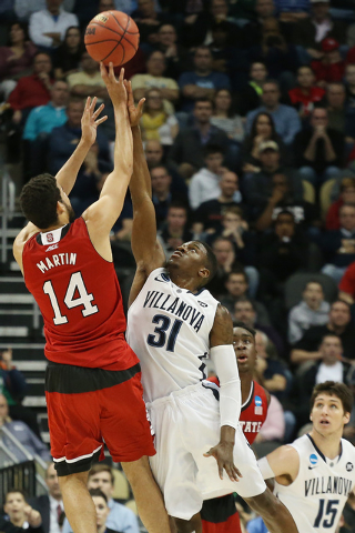 Mar 21, 2015; Pittsburgh, PA, USA; North Carolina State Wolfpack forward Caleb Martin (14) shoots the ball as Villanova Wildcats guard Dylan Ennis (31) defends during the first half in the third r ...