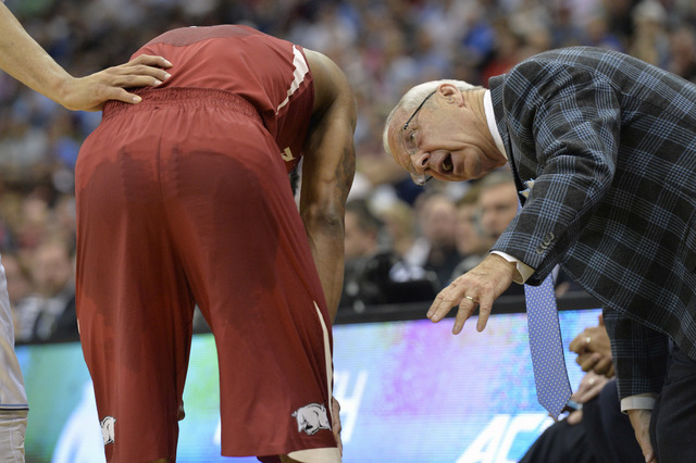 Mar 21, 2015; Jacksonville, FL, USA; North Carolina Tar Heels head coach Roy Williams checks on Arkansas Razorbacks guard Anthlon Bell (5) after an injury to Bell in the first half of a game in th ...