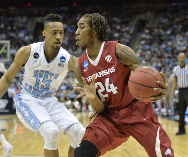 Mar 21, 2015; Jacksonville, FL, USA; North Carolina Tar Heels forward J.P. Tokoto (13) defends as Arkansas Razorbacks guard Michael Qualls (24) drives the ball in the first half of a game in the t ...