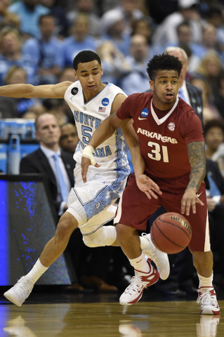 Mar 21, 2015; Jacksonville, FL, USA; North Carolina Tar Heels guard Marcus Paige (5) tries to steal the ball from Arkansas Razorbacks guard Anton Beard (31) in the second half of a game in the thi ...