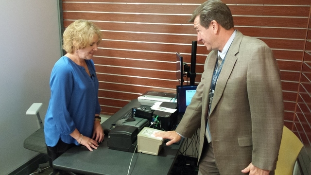 Rick Jackson, stakeholder manager for the Transportation Security Administration at McCarran International Airport, has his fingerprints electronically scanned by Lorie Denkers in a demonstration  ...
