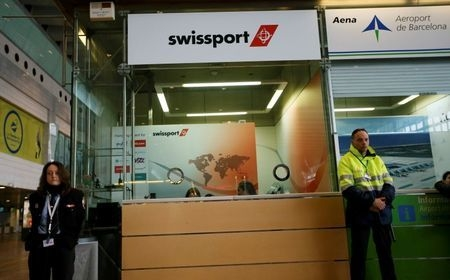 Officials stand by at the Swissport counter which handles Germanwings flights at Barcelona's El Prat airport, March 24, 2015. (Reuters/Albert Gea