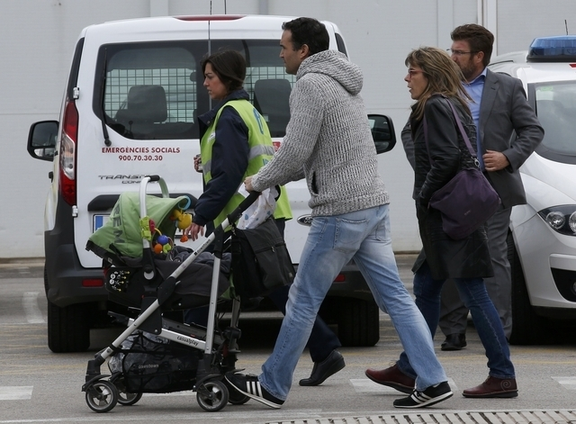 Family members of passengers killed in Germanwings plane crash are escorted by a helper as they arrive at Barcelona's El Prat airport March 24, 2015. Lufthansa's budget carrier Germanwings confirm ...