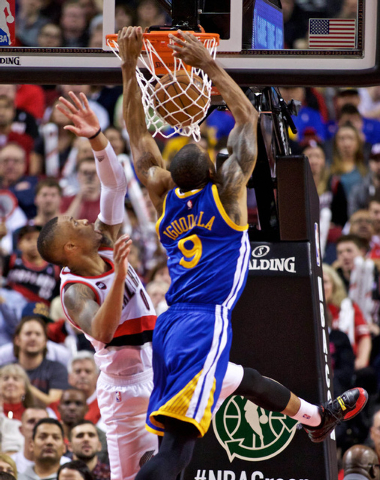 Mar 24, 2015; Portland, OR, USA; Golden State Warriors guard Andre Iguodala (9) dunks over Portland Trail Blazers guard Damian Lillard (0) during the fourth quarter at the Moda Center. Mandatory C ...