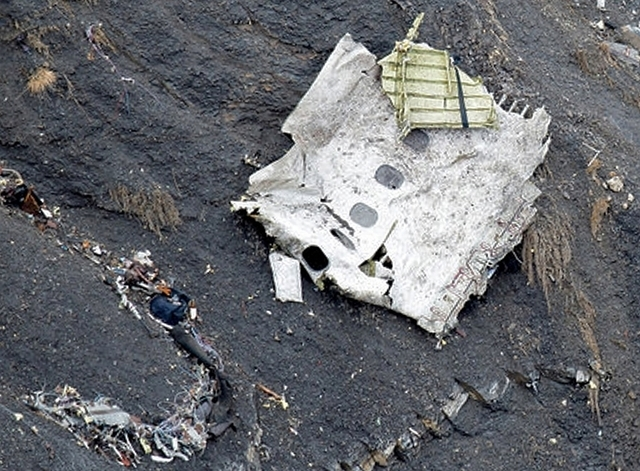 A photo released March 25, 2015, by the French Interior Ministry shows a rescue worker near a fuselage section amongst the debris at the crash site of an Airbus A320, near Seyne-les-Alpes. French  ...