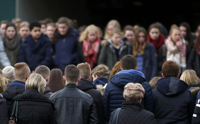People hold a minute of silence outside Joseph-Koenig-Gymnasium high school in Haltern am See, March, 26, 2015. The deaths of 16 teenage students and two young teachers in the Germanwings plane cr ...