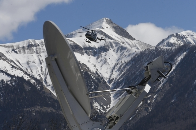 A rescue helicopter from the French Gendarmerie lands behind a media satellite dish seen during operations near the crash site of an Airbus A320, in Seyne-les-Alpes, March 26, 2015. Voice recordin ...