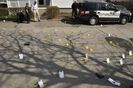 Evidence markers are seen on a street where Tamerlan and Dzhokhar Tsarnaev engaged in a gunfight with police in this undated handout evidence photo provided by the U.S. Attorney's Office in Boston ...