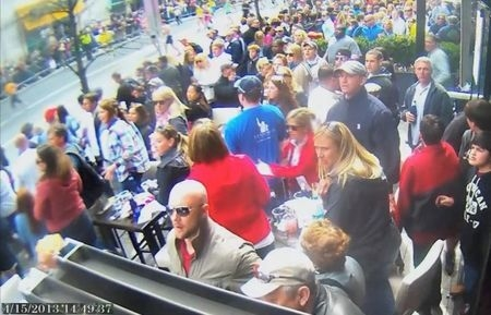 A still image captured from surveillance video at the Boston Marathon shows the scene moments before a second bomb exploded as a man, marked with a circle by prosecutors, top right, and identified ...