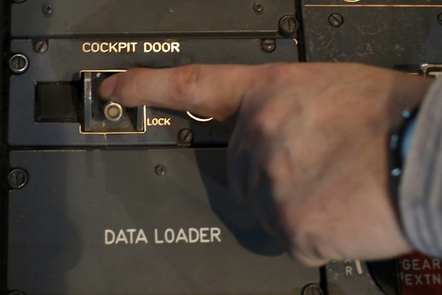 A person moves the switch of the cockpit door locking system inside a flight simulator of an Airbus A320 in Vienna on March 26, 2015. A co-pilot suspected of deliberately crashing a Germanwings je ...