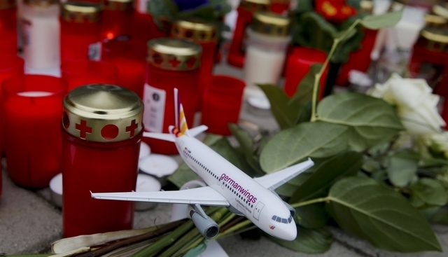 A model of a Germanwings plane is placed among flowers and lit candles in Cologne Bonn airport, March 26, 2015. The co-pilot suspected of deliberately crashing a Germanwings jet into the French Al ...