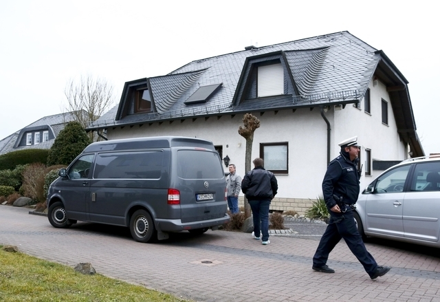 A German police officer walks in front of a house believed to belong to crashed Germanwings flight 4U 9524 co-pilot Andreas Lubitz in Montabaur, March 26, 2015. The 28-year-old co-pilot is suspect ...