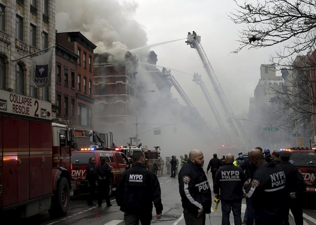 New York City Fire Department firefighters and police stand by as firefighters fight a fire at a residential apartment building in New York City March 26, 2015. The residential apartment building  ...