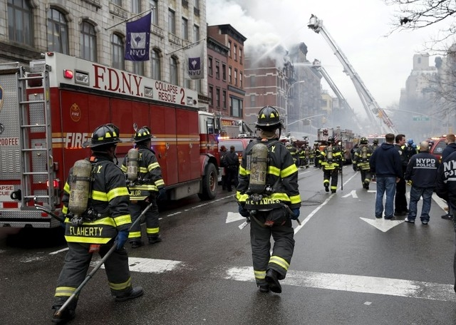 New York City Fire Department firefighters walk on 2nd Avenue towards the site of where a residential apartment was engulfed in flames in New York City March 26, 2015. (REUTERS/Mike Segar)