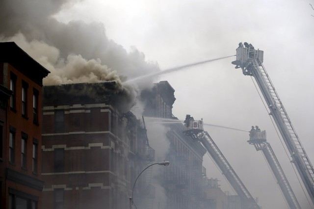 New York City Fire Department firefighters battle fire at the site of a residential apartment building in New York City's East Village neighborhood March 26, 2015. (REUTERS/Mike Segar)