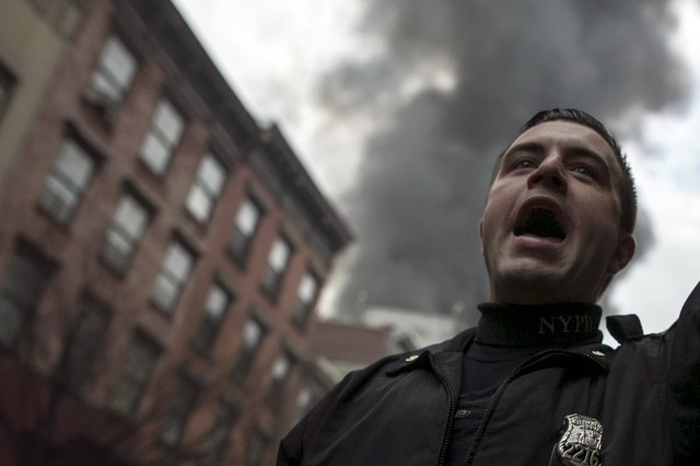 A New York Police Department (NYPD) officer shouts towards residents while clearing the site of a building fire in the East Village neighborhood of New York City on March 26, 2015. (REUTERS/Ben Hider)