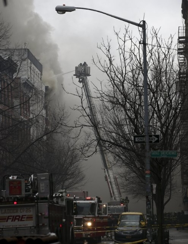 New York City Fire Department firefighters battle fire at a residential apartment building in New York City's East Village neighborhood March 26, 2015. The residential apartment building collapsed ...