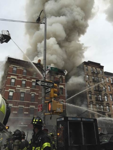 Fire officials are seen outside a building which collapsed and burst into flames at Second Avenue and East 7th Street in New York's East Village in this picture courtesy of Andrea Scarantino taken ...