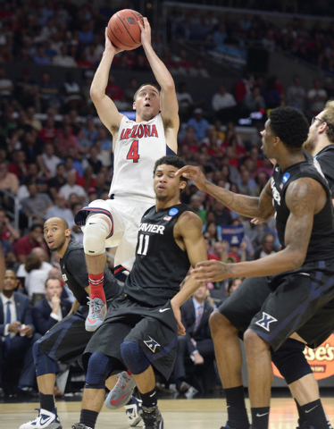 Mar 26, 2015; Los Angeles, CA, USA; Arizona Wildcats guard T.J. McConnell (4) moves to the basket against Xavier Musketeers guard Dee Davis (11) during the first half in the semifinals of the west ...