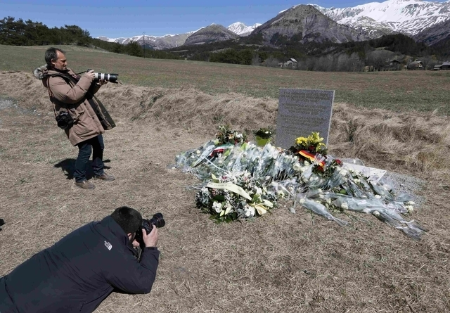 Photographers take pictures at the memorial for the victims of the air disaster in the village of Le Vernet, near the crash site of the Airbus A320 in French Alps March 27, 2015. A young German co ...