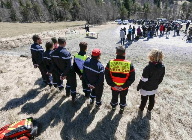 Rescuers stand ready as relatives pay their respects at the memorial for the victims of the air disaster in the village of Le Vernet, near the crash site of the Airbus A320 in French Alps March 27 ...