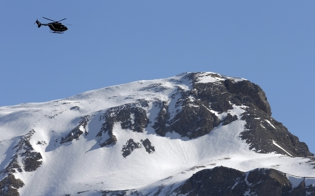 A rescue helicopter from the French Gendarmerie flies over the snow-covered French Alps during operations near the crash site of the Germanwings Airbus A320, near Seyne-les-Alpes, March 28, 2015.  ...