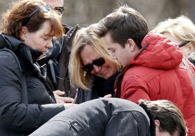 People identified by the mayor of Le Vernet as family members of the pilot of the Germanwings Airbus A320 react as they pay their respects at the memorial for the victims of the air disaster in th ...