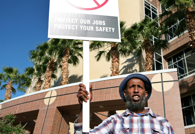 "Union Cab driver Jamal Lis holds a sign that says, ""Protect our jobs, protect your safety"" during a rally outside Grant Sawyer Building Monday, March 30, 2015, in Las Vegas. Dozens of So ..."