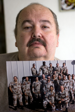 Former Area 51 worker Fred Dunham holds up a photograph while standing in his home Wednesday, Aug. 13, 2008, that depicts himself, standing at left, with several of his coworkers in 1988. Due to D ...