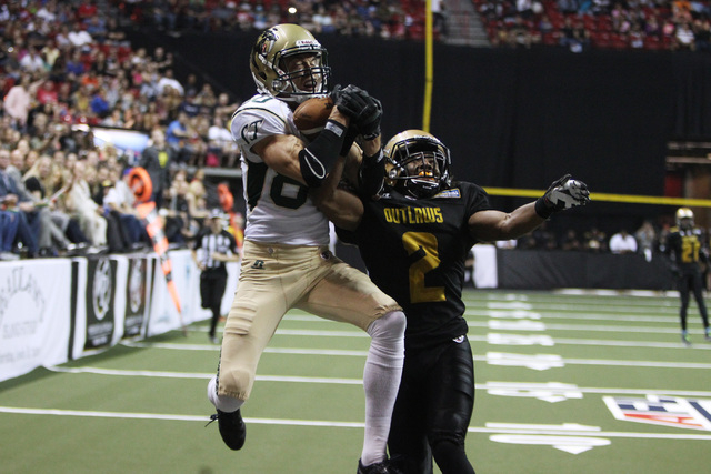 San Jose SaberCats wide receiver Ben Nelson pulls in a touchdown pass under coverage by Las Vegas Outlaws defensive back Donovan Henley during the Outlaws inaugural Arena Football League game Mond ...