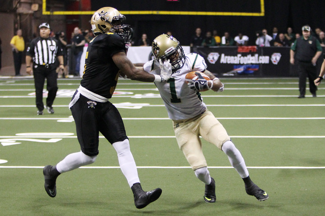 Las Vegas Outlaws defensive back Dee Webb grabs the face mask of San Jose SaberCats wide receiver Reggie Gray during the Outlaws inaugural Arena Football League game Monday, March 30, 2015, at the ...