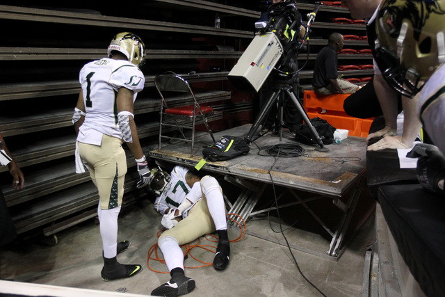 San Jose SaberCats wide receiver Reggie Gray checks on fellow wide receiver Adron Tennell after Tennell flipped over the boards during the Las Vegas Outlaws inaugural Arena Football League game Mo ...