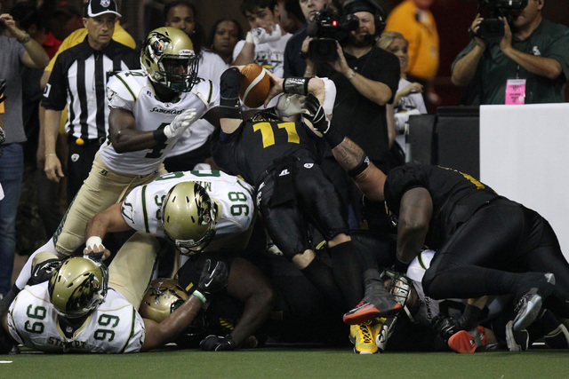 Las Vegas Outlaws quarterback J.J. Raterink leaps over the goal line for Outlaws first ever touchdown during the Outlaws inaugural Arena Football League game Monday, March 30, 2015, against the Sa ...
