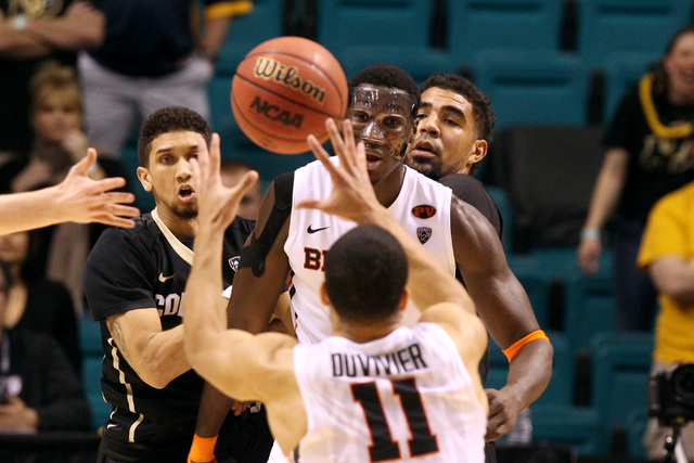Oregon State forward Daniel Gomis passes to guard Malcolm Duvivier as Colorado guard Askia Booker, left, and forward Josh Scott look on during the first half of their Pac-12 Conference tournament  ...
