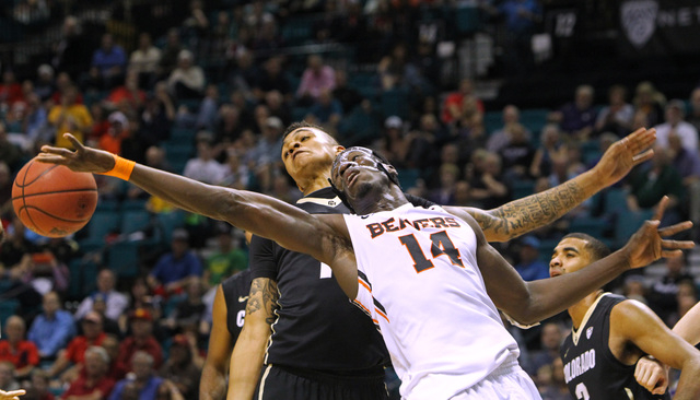 Colorado guard Dustin Thomas leans back as Oregon State forward Daniel Gomis reaches for a rebound during the second half of their Pac-12 Conference tournament game Wednesday, March 11, 2015, at t ...